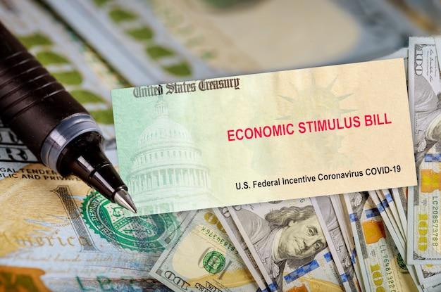 Programa de alívio de estímulo econômico bill cheques de alívio financeiro de coronavírus do governo notas de dólar em dinheiro na bandeira americana pandemia global covid 19
