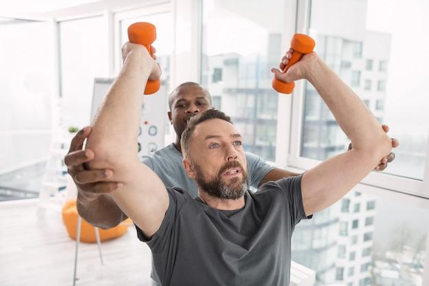 Programa individual. homem bonito sério levantando halteres enquanto se exercita com um personal trainer