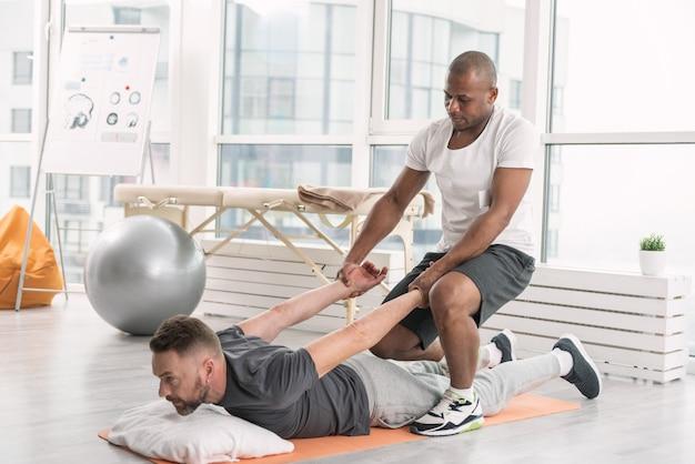 Programa individual. um bom treinador profissional ajudando seu cliente a realizar um exercício enquanto tem um treinamento especial com ele