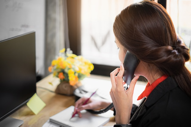 Programação da nota da mulher de negócio no livro e fala com o cliente pelo telefone.