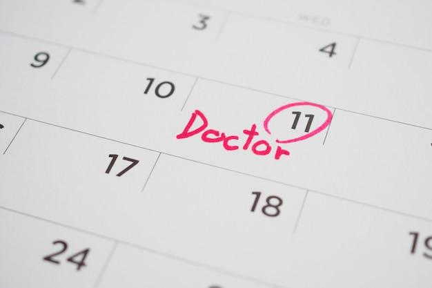 Programação de consulta médica importante escrita na data da página do calendário em branco close-up