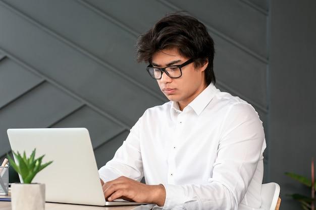 Programador asiático trabalhando em laptop no escritório