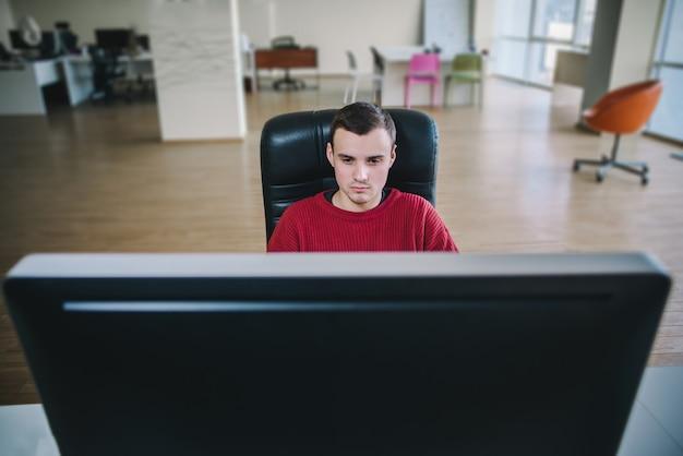 Programador de hipster bonito jovem sentado em um monitor de computador grande e trabalho. escritório de fluxo de trabalho