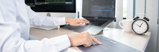 Programador de mulher asiática digitando códigos-fonte de programação no computador no escritório, conceito de desenvolvedor web freelance.