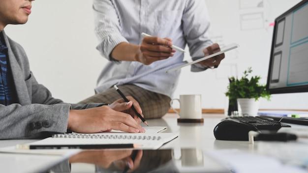 Programador e web designer trabalhando com desenvolvimento no computador e tablet.