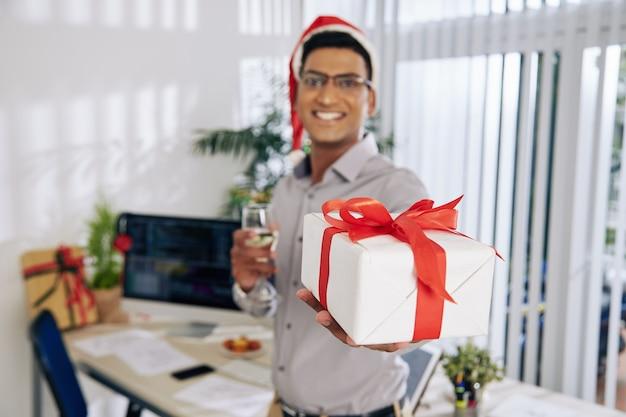 Programador feliz bebendo champanhe e estendendo a mão com um presente de natal