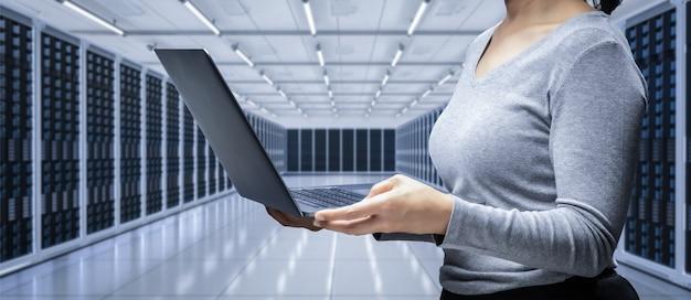 Programador feminino com notebook na sala do servidor