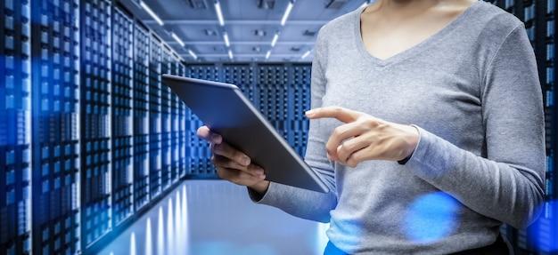 Programador feminino com tablet digital na sala do servidor
