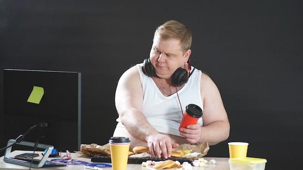 Programador gordo trabalha em casa remotamente em um computador, uma pessoa trabalha e come ao mesmo tempo, fundo preto isolado