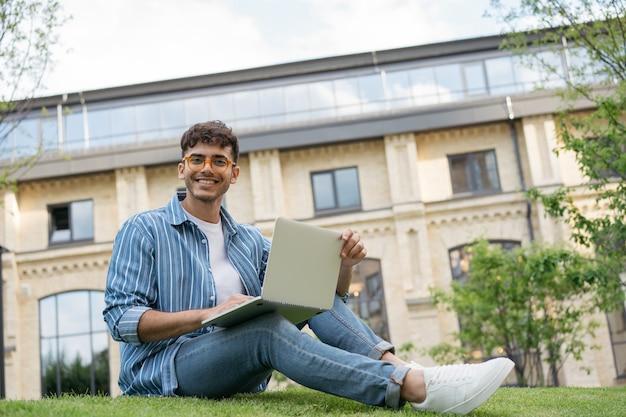 Programador indiano sorridente usando laptop e trabalhando em projeto freelance online sentado no parque