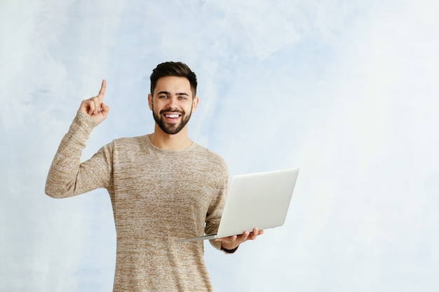 Programador masculino com laptop e dedo indicador levantado na cor