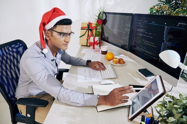 Programador sério com chapéu de papai noel, verificando o diagrama de blocos na tela do computador tablet ao trabalhar na mesa do escritório