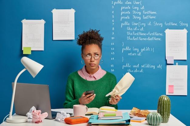 Programadora pensativa, de pele escura, com expressão de vergonha no rosto, tenta lembrar o número de telefone do parceiro com documento em papel
