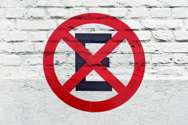 Proibido estacionar: sinal de trânsito estampado na parede branca, como grafite