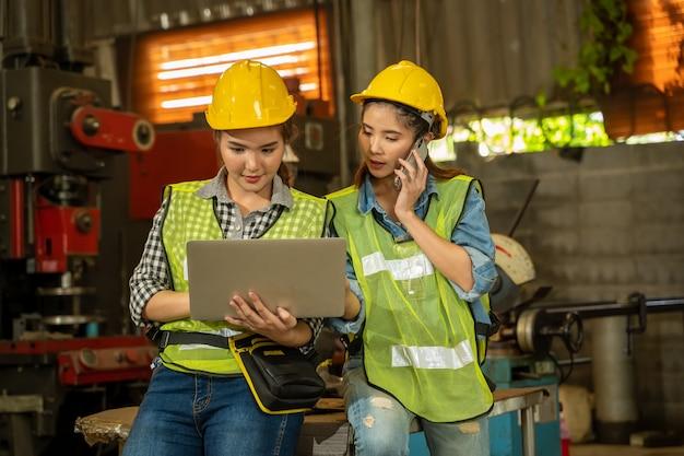 Projetando mulheres que usam um laptop que trabalha na fábrica, conceito da tecnologia de fábrica.