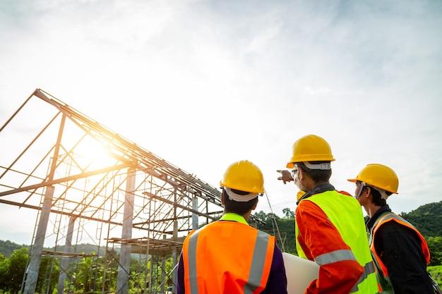 Projete a equipe de observação do técnico do controle do trabalhador nos trabalhadores da construção que vestem a roupa de segurança e que discutem no canteiro de obras que verifica o portátil do escritório no canteiro de obras.