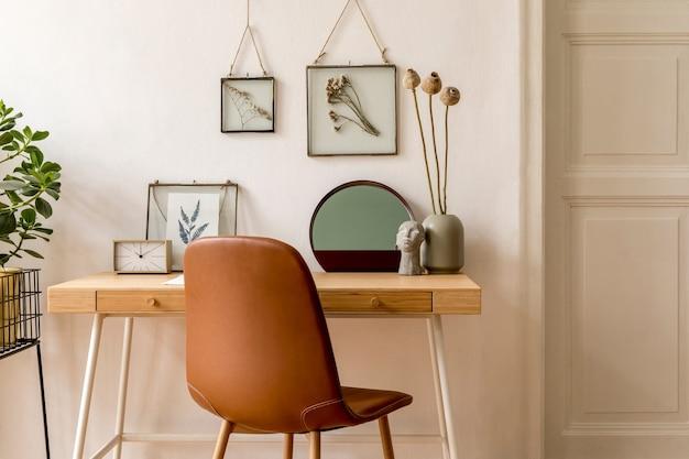 Projete o interior escandinavo de um escritório doméstico com várias molduras para fotos, mesa de madeira, cadeira marrom, plantas, escritório e acessórios pessoais. encenação em casa neutra e elegante.