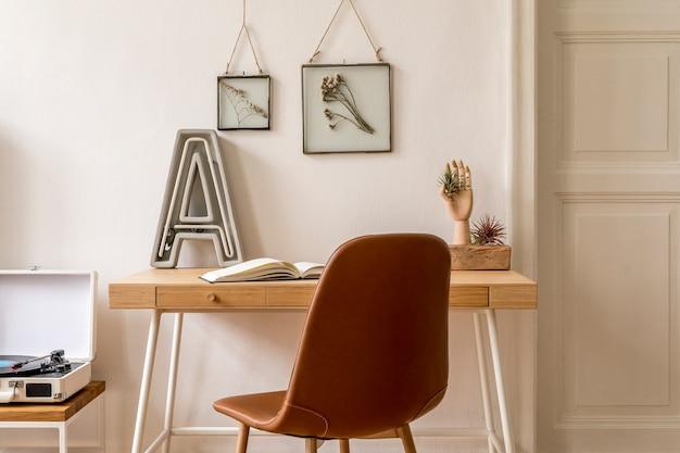 Projete o interior escandinavo de um escritório em casa com várias molduras para fotos, mesa de madeira, cadeira marrom, carta de néon, escritório e acessórios pessoais. encenação em casa neutra e elegante.