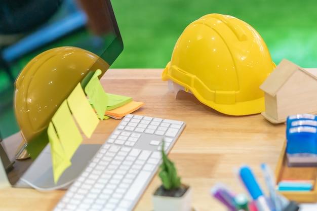 Projete o objeto do construtor da casa do contratante de construction na mesa de escritório com o computador para o conceito moderno do contratante da construção do colaborador da casa.