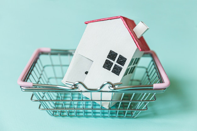 Projete simplesmente com a casa branca diminuta do brinquedo e o cesto de compras na mercearia do supermercado isolado no fundo azul. conceito de casa de sonho de seguro de propriedade de hipoteca copie o espaço