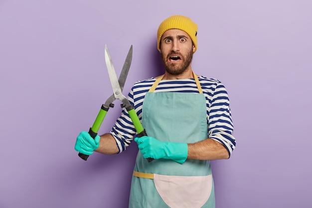 Projetista ou jardineiro insatisfeito segura tesouras de jardinagem, vai cortar arbustos verdes e usa chapéu amarelo