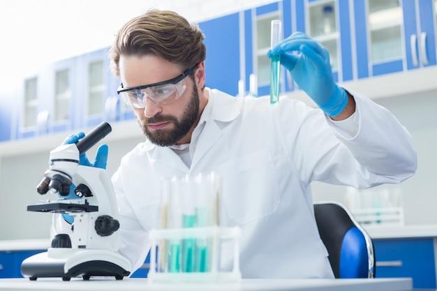 Projeto científico. trabalho sério e inteligente segurando um tubo de ensaio e olhando no microscópio enquanto trabalhava em seu projeto