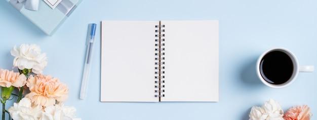 Projeto concpet da saudação do dia das mães com flor cravo, ideia de presente de feriado e caderno diário no fundo da mesa da mãe.