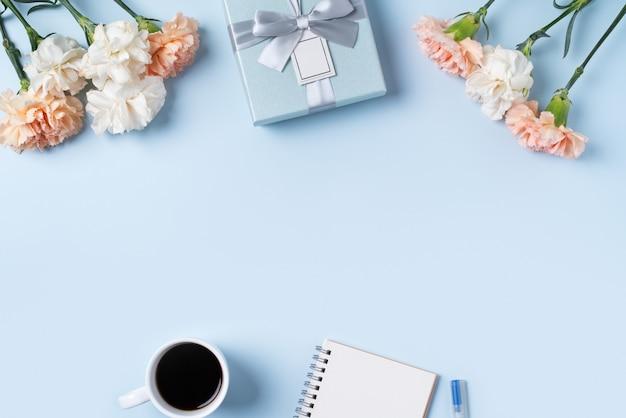 Projeto concpet de saudação de dia das mães com flor cravo, ideia de presente de feriado e caderno diário no fundo da mesa das mães.
