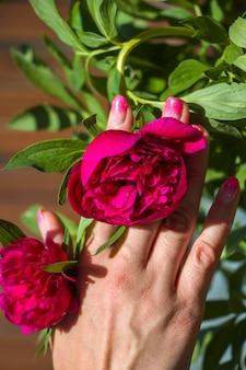 Projeto criativo manicure rosa engraçado com a inscrição party dance. estilo de festa de verão. mãos femininas com unhas de glitter vibrante segurando píon de flor cor de vinho.