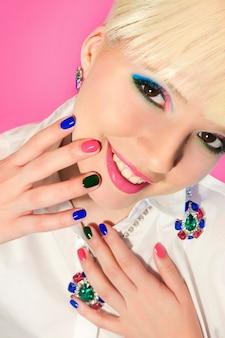 Projeto da arte do prego curto colorido na moda na mão feminina fechar com decoração no rosto. esmalte rosa verde azul.