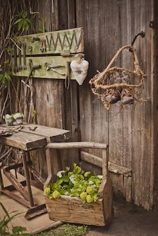 Projeto da zona de foto em estilo rústico, portas de madeira velha e placas com ferramentas e flores de primavera.