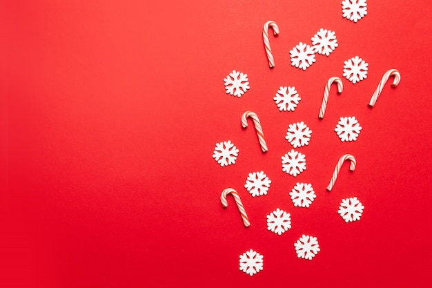 Projeto de ano novo de natal com flocos de neve brancos com muitos bastões de doces em vermelho pastel