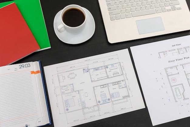 Projeto de casa com laptop e xícara de café em preto