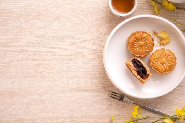 Projeto de conceito de feriado do festival do meio outono de bolo da lua, bolos lunares, conjunto de chá em uma mesa de madeira brilhante com espaço de cópia, vista superior, postura plana, foto aérea