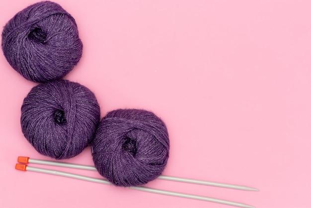 Projeto de confecção de malhas em andamento. um pedaço de tricô com novelo de lã e agulhas de tricô.