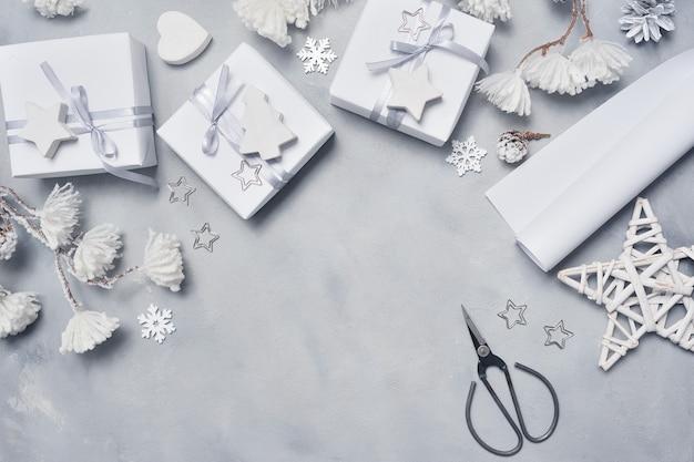Projeto de fronteira um cartão de natal com caixas de presente de natal, tesouras, cones, estrela, flocos de neve.