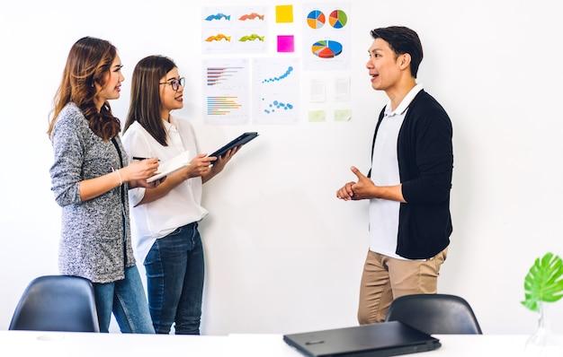 Projeto de ideia de inicialização de reunião de negócios asiática no escritório com gráficos na parede