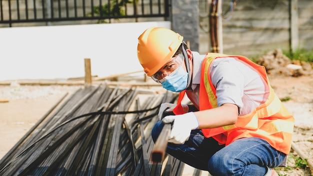 Projeto de indústria de segurança de trabalho de homem empreiteiro de engenheiro, verificar investigando o tamanho e qualidade do aço usado em canteiro de estruturas de construção de edifícios.