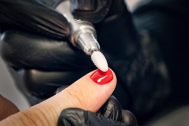 Projeto de manicure masculina. o mestre faz uma manicure. o conceito de cuidado profissional das unhas. close das mãos da manicure no trabalho. um homem faz manicure. manicure masculina.