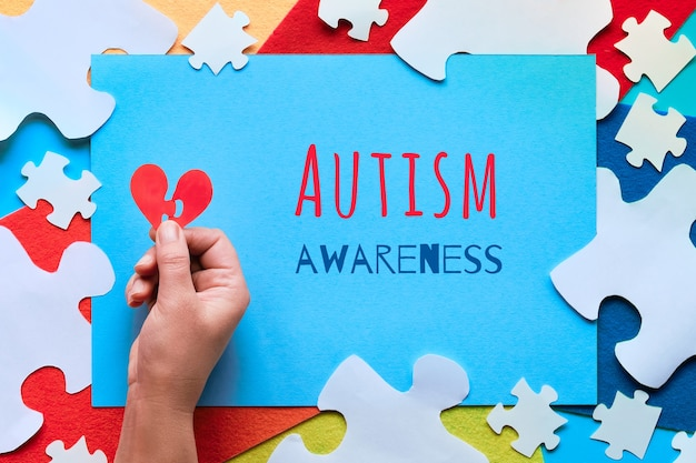Projeto de papel do conceito, texto conscientização do autismo elementos de quebra-cabeça em peças de feltro, vista superior.