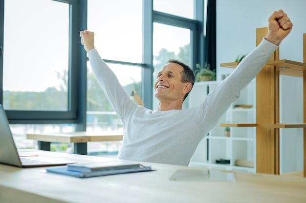 Projeto de sucesso. homem de boa aparência, positivo, encantado, sentado à mesa e segurando as mãos para cima, enquanto fica feliz com seu projeto de sucesso