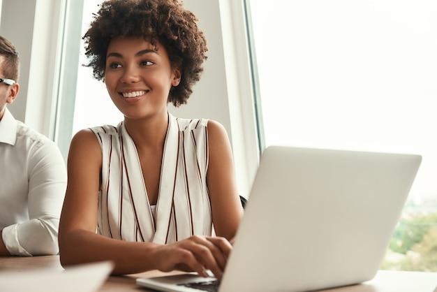 Projeto de sucesso, jovem e bela mulher afro-americana trabalhando em um laptop e desviando o olhar com