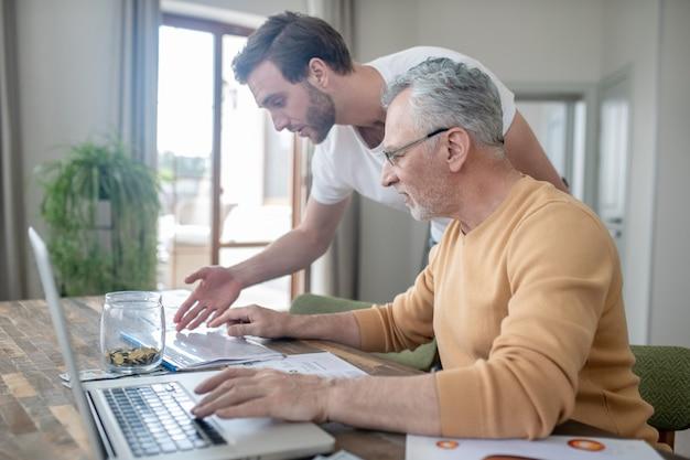 Projeto de trabalho. dois homens trabalhando juntos em um projeto e parecendo interessados