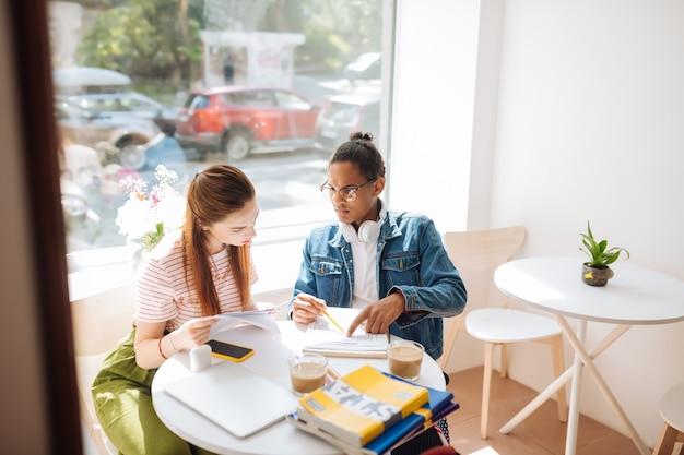 Projeto de trabalho. mulher concentrada inclinando a cabeça enquanto olha as notas