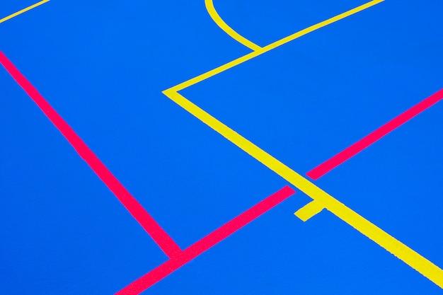 Projeto de um campo de esportes, com fundo azul e linhas brancas vermelhas e amarelas, criando estranhas linhas retas e curvas, para usar com espaço de cópia.
