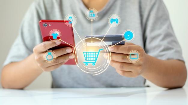Projeto digital de um carrinho de compras com ícones ao redor e alguém fazendo compras online em segundo plano.