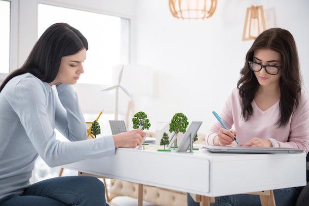 Projeto eco. mulher e estudante pensativas e imóveis, escrevendo e ajudando-se mutuamente na tarefa Foto Premium
