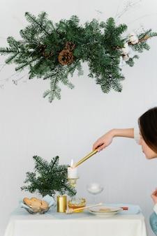 Projeto estético para o natal com guirlanda de suspensão de pinho nobilis, velas e decorações de mesa.