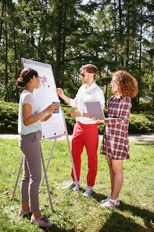 Projeto importante. homem sério e estiloso em pé perto do quadro e discutindo seu projeto com os amigos