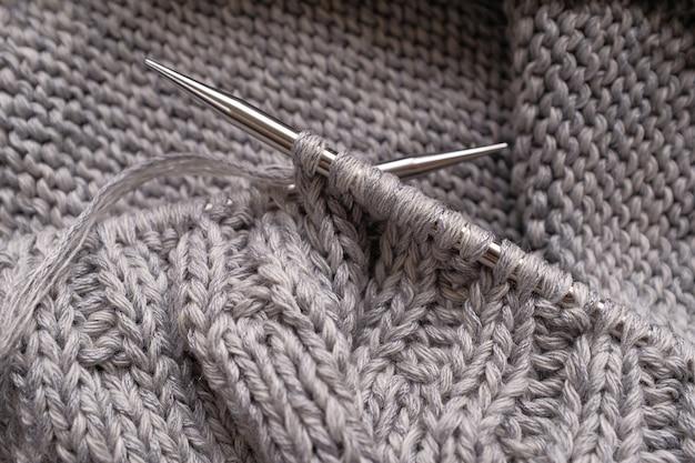 Projeto incompleto de tricô com agulhas de metal. fazendo tricô um suéter de lã cinza.